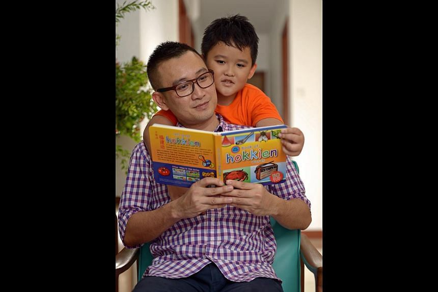 Mr Koh Kuan Eng and his nephew Kaizer Koh, now seven, with the dialect picture book he created.--ST PHOTOS: DESMOND WEE
