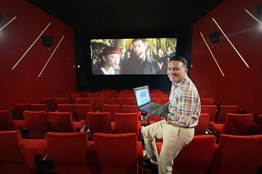NEW METHOD: Cathay Organisation CEO Suhaimi Rafdi showing how the cinema experience – lights, curtains and movie projection – can all be controlled remotely from a laptop.-- ST PHOTOS: ALPHONSUS CHERN