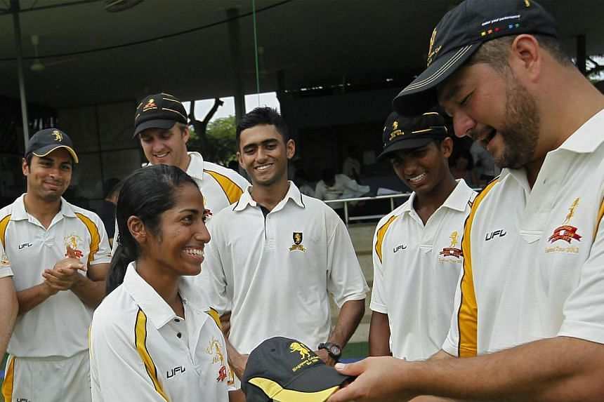 Diviya G.K., who received the club cap from Singapore Cricket Club captain Richard Stapley-Oh, should play abroad to further hone her skills, say pundits. -- ST PHOTO: MARK CHEONG