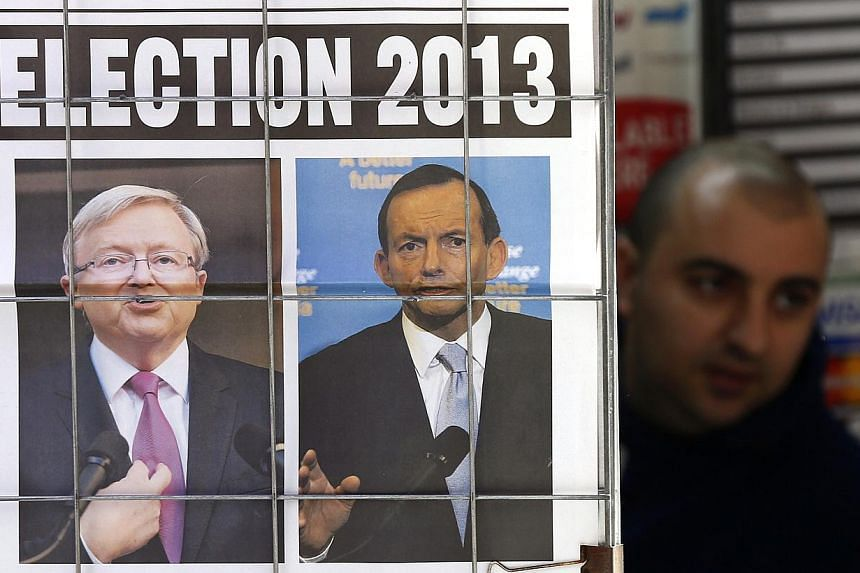 An advertisement for a newspaper with pictures of Australian Prime Minister Kevin Rudd (L) and opposition leader Tony Abbott in central Sydney on Aug 5, 2013. Mr Rudd called a Sept 7 general election on Aug 4, barely six weeks after he toppled former