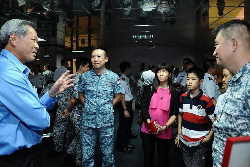 Dr Ng Eng Hen interacting with medal recipients and their family members after the presentation ceremony. For three months, members of the Combined Task Force (CTF) 151 remained alert and thwarted numerous piracy attempts in the Gulf of Aden.&nb