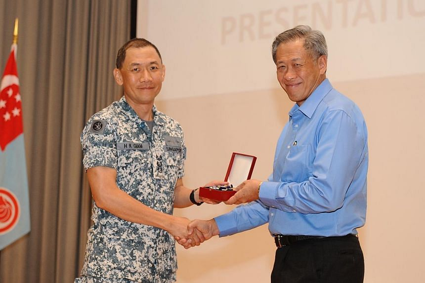 Colonel Giam Hock Koon, 47, receiving the SAF Overseas Service Medal from Minister for Defence Dr Ng Eng Hen at the presentation ceremony. For three months, members of the Combined Task Force (CTF) 151 remained alert and thwarted numerous piracy