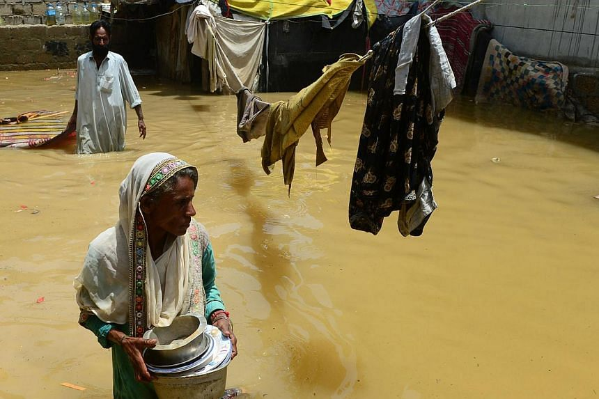 Pakistani woman walks through floodwaters following heavy monsoon rain in Karachi on Monday, August 5, 2013. Monsoon rain and floods have killed at least 58 people across Pakistan and affected tens of thousands of others, officials said on Monday, wa