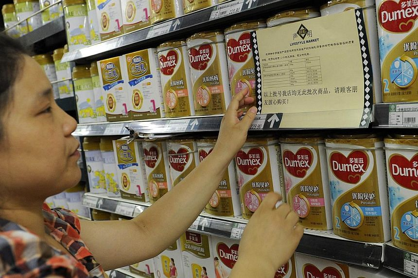 A woman checks a guarantee announcement on a shelf of Dumex baby formula, which uses the New Zealand dairy Fonterra as its raw material supplier, at a supermarket in Hefei, north China's Anhui province, on Aug 5, 2013. -- FILE PHOTO: AFP
