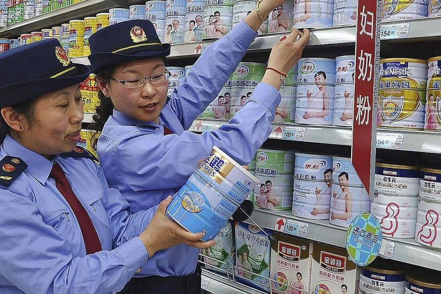 Chinese commercial law enforcement personnel inspect milk powder products at a supermarket in Lianyungang, Jiangsu province on Aug 6, 2013. -- PHOTO: REUTERS