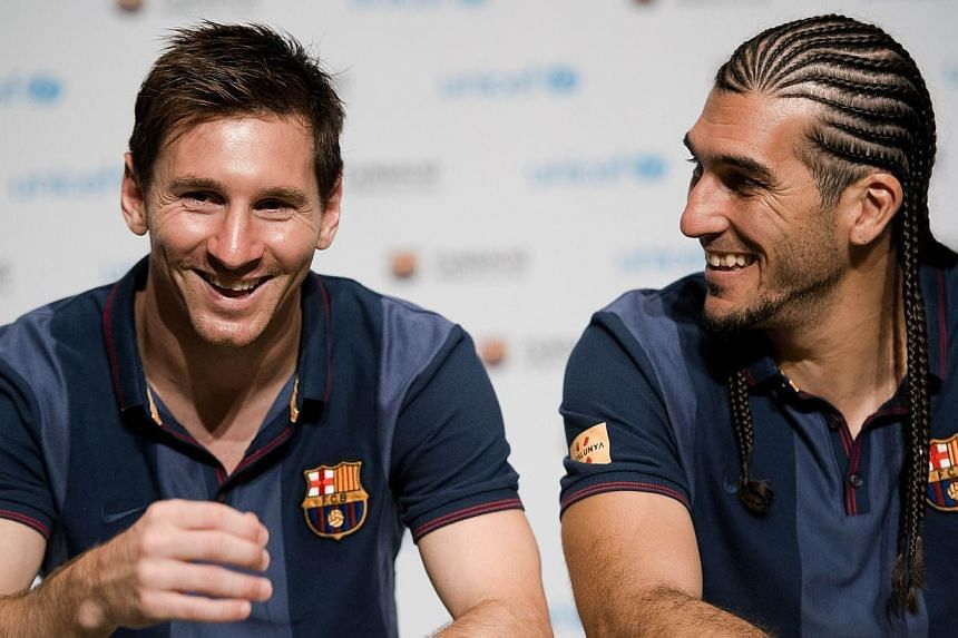 Barcelona football player Lionel Messi (left) and goalkeeper Jose Manuel Pinto answer questions from disabled children at the Okura hotel in Bangkok on Tuesday, Aug 6, 2013. Messi on Tuesday attributed his stunning achievements to hard work and sacri