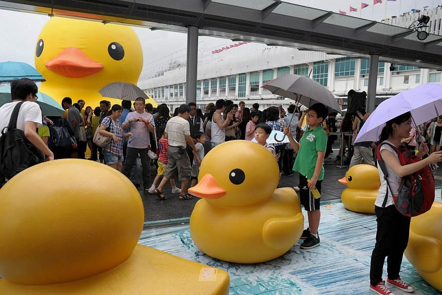 Visitors pose with ducks as thousands of others crowd the waterfront on the last day to see a giant 16.5m-tall duck (back left), conceived by Dutch artist Florentijn Hofman, in Hong Kong on Sunday, June 9, 2013. -- FILE PHOTO: AFP