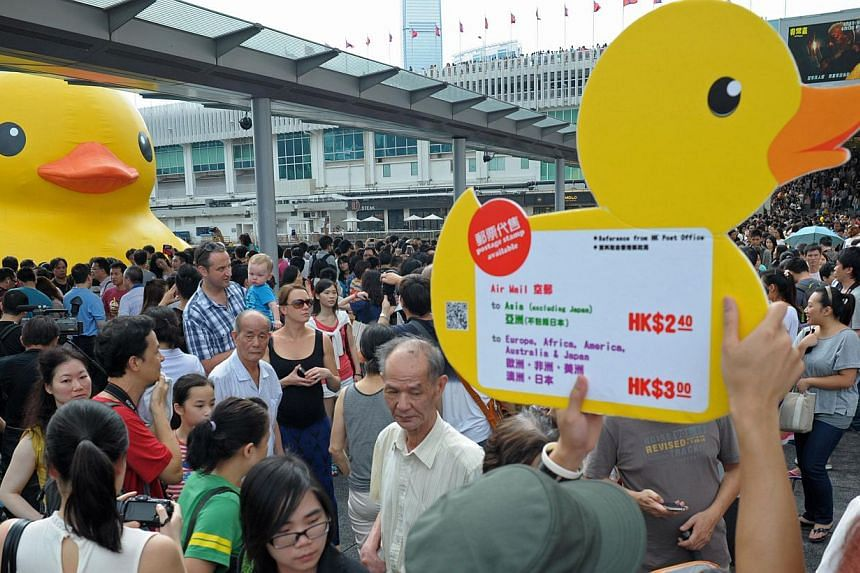 Thousands of people crowd the waterfront on the last day to see a giant rubber duck (left), conceived by Dutch artist Florentijn Hofman, in Hong Kong on Sunday, June 9, 2013.-- FILE PHOTO: AFP