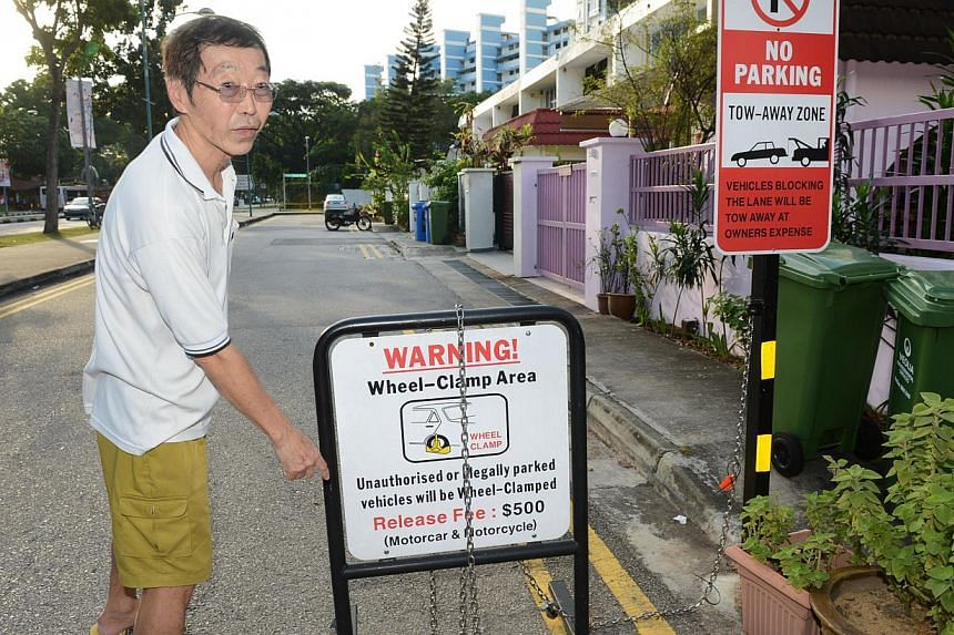 Mr Lim, a Jalan Mas Puteh resident, pointing to a sign put up to prevent illegal parking there.