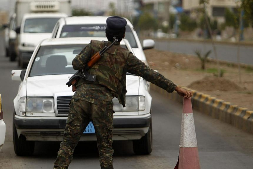 A police trooper is seen manning a checkpoint in Sanaa on Aug 5, 2013. Britain has issued the highest possible security alert to British shipping companies operating off the coast of Yemen, an expert said on Tuesday, Aug 6, 2013, amid a worldwide ter