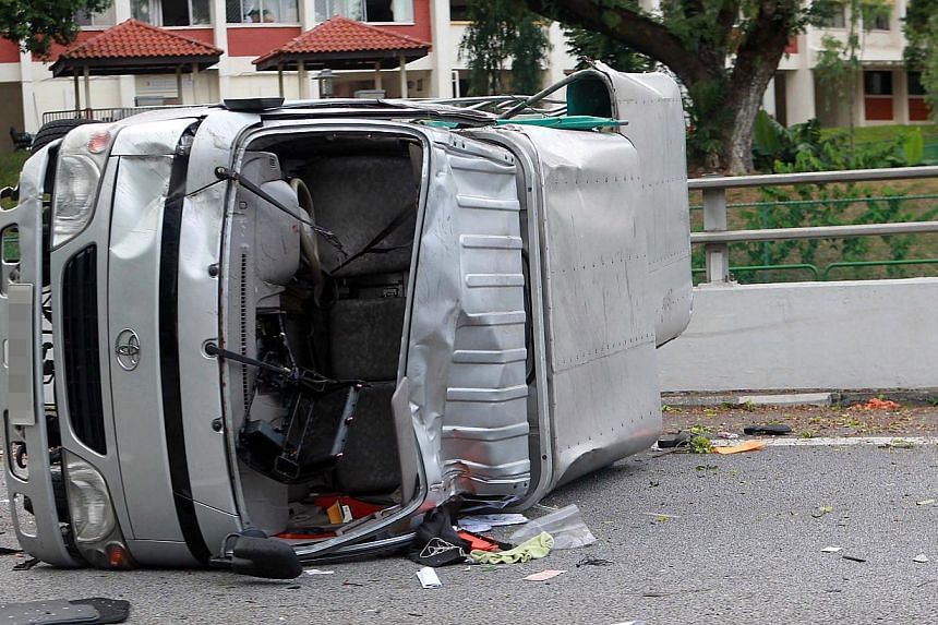 This lorry, which was carrying workers from China and India, was left lying on its side after a BMW smashed into its back on Aug 4, 2013. Migrant workers group Transient Workers Count Too renewed its calls for workers to be ferried in buses and not l