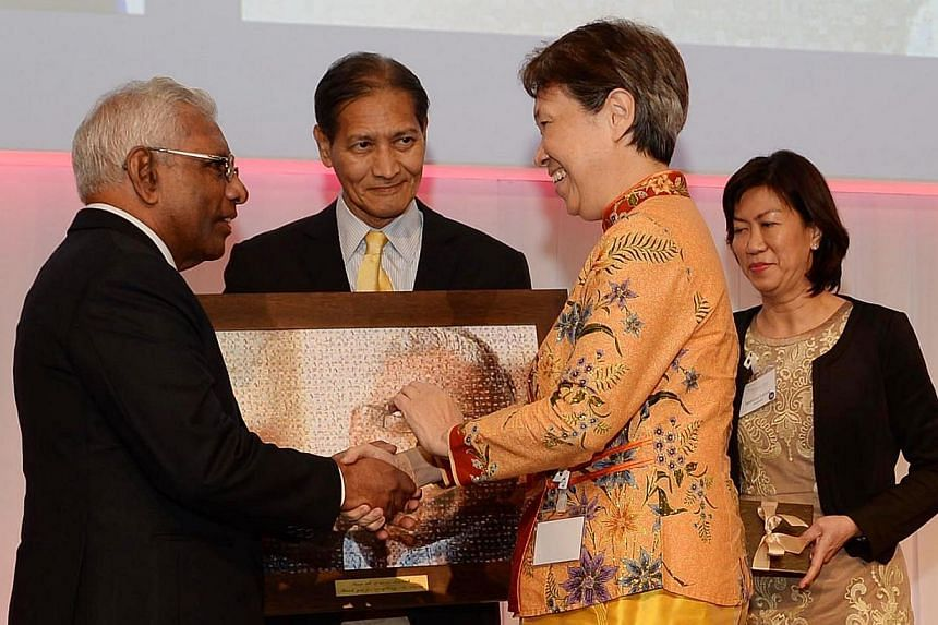 Mr S. Dhanabalan (left) being presented with a picture mosiac made up of pictures of its staff by Temasek CEO Ho Ching at theTemasek 39th anniversary dinner at the Ritz Carlton on Tuesday, Aug 6, 2013. Prime Minister Lee Hsien Loong led the tributes