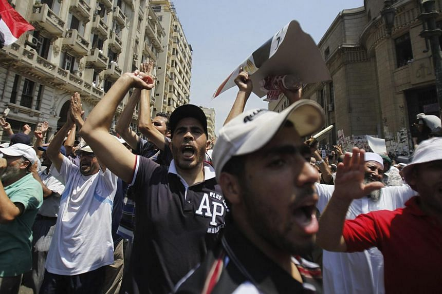 Members of the Muslim Brotherhood and supporters of deposed Egyptian President Mohamed Mursi shout slogans as they close the roads in front of the courthouse and the Attorney General's office during a protest in downtown Cairo on Aug 5, 2013. -- FILE