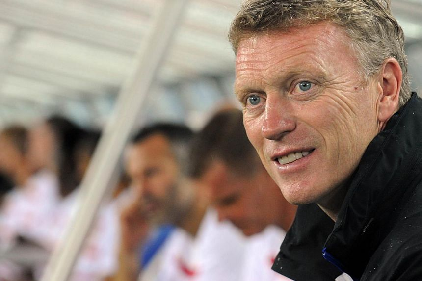Manchester United head coach David Moyes (right) smiles on the bench prior to the friendly football match against Yokohama Marinos in Yokohama, Kanagawa prefecture on July 23, 2013. -- FILE PHOTO: AFP