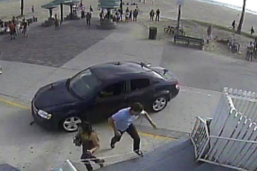 In this still frame made from security camera footage from Snapchat headquarters, pedestrians scatter as a car drives through a packed afternoon crowd along the Venice Beach boardwalk in Los Angeles, on Saturday, Aug 3, 2013. -- FILE PHOTO: AP