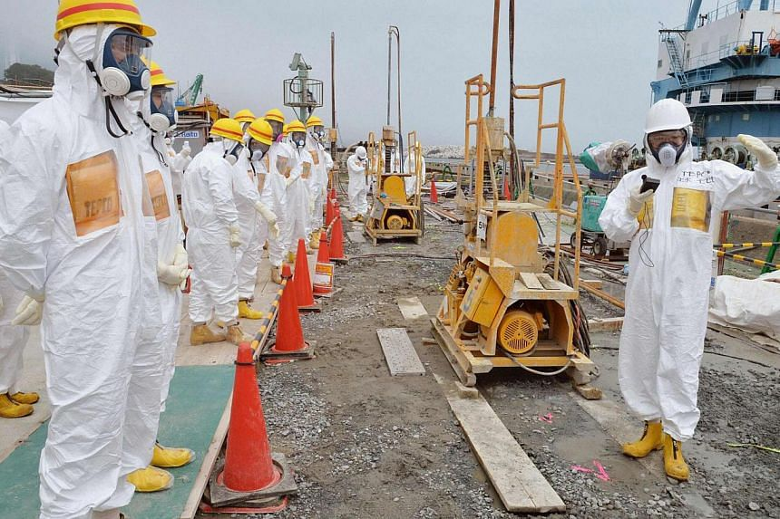 Members of a Fukushima prefecture panel inspect the construction site of the shore barrier near the No.1 and No.2 reactor building of the Fukushima Daiichi nuclear power plant , in this photo released by Kyodo on Aug 6, 2013. -- PHOTO: REUTERS