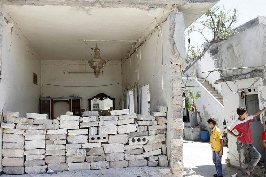 Boys stand near a damaged house in Azaz, near Aleppo on Aug 6, 2013. Fierce clashes broke out on Wednesday, Aug 7, 2013, on the edge of the northern city of Aleppo, a day after rebels overran a nearby air base, while a deadly blast rocked Raqa city,