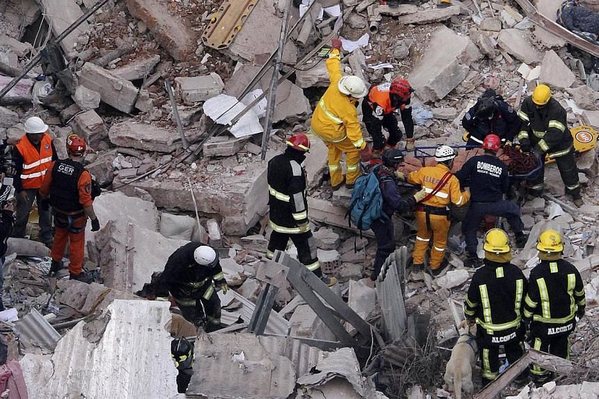 Argentine authorities on Wednesday combed through the charred ruins of an apartment building destroyed by an explosion and fire that left at least 10 people dead. - PHOTO:REUTERS