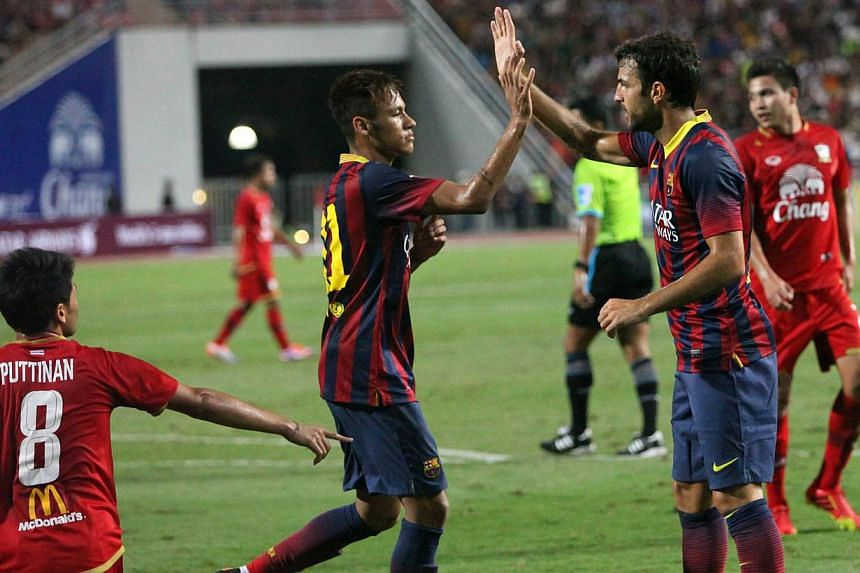 Barcelona's Neymar (centre) celebrates with teammate Cesc Fabregas after scoring against Thailand's national team during their friendly football match at Rajamangala national stadium in Bangkok on Wednesday, Aug 7, 2013. Brazilian wonderkid Neymar sc