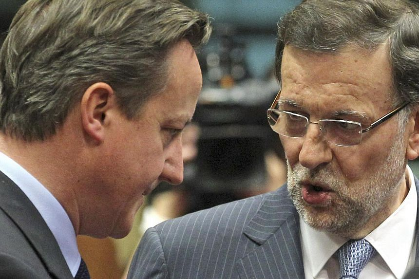 """British Prime Minister David Cameron (left) speaks with Spain's Prime Minister Mariano Rajoy during a round table meeting at an EU summit in Brussels on Thursday, June 27, 2013. Mr Cameron has spoken to his Spanish counterpart Mr Rajoy to raise """"seri"""