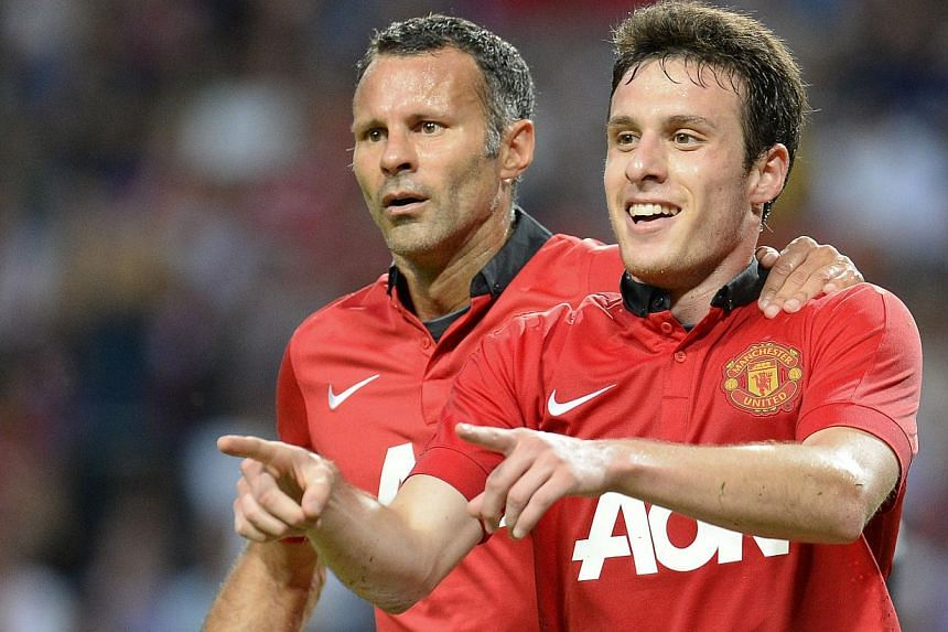 Manchester United's Chilean striker Angelo Henriquez (right) celebrates with teammate midfielder Ryan Giggs after scoring during the friendly football match AIK v Manchester United on Aug 6, 2013 at the Friends Arena in Solna, near Stockholm, Sweden.