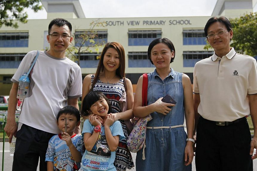 Mr Leong (left) and wife Sarah Chen, 30, with their daughter Gracie, six, who succeeded in getting a place at South View Primary School during Phase 2C, and son Lucas, four. With them are Ms Wang Wan (third from left), 39, and her husband Stephen Hoo