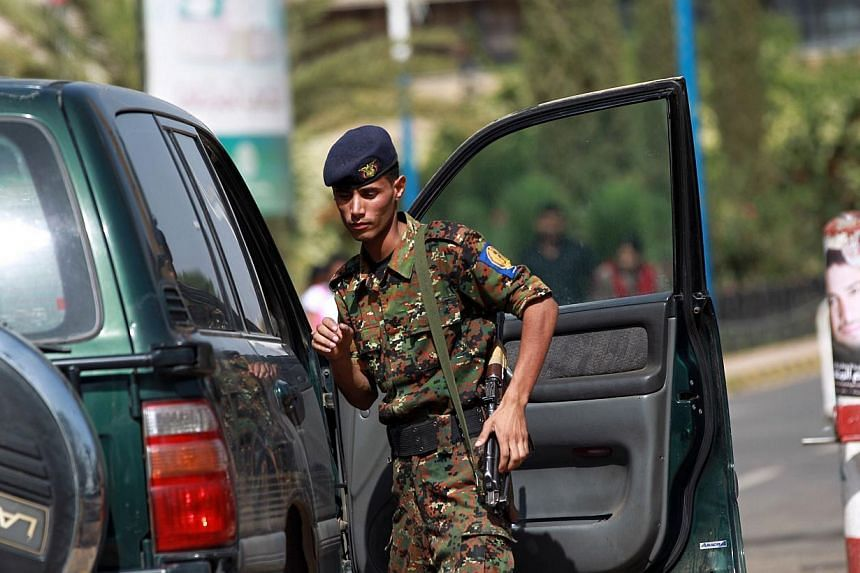 A police trooper inspects a vehicle at the entrance of the Sanaa International Airport on Wednesday, Aug 7, 2013. Al-Qaeda in Yemen was hit by a fresh strike from a US drone on Wednesday which left seven militants dead, tribal sources said, a day aft