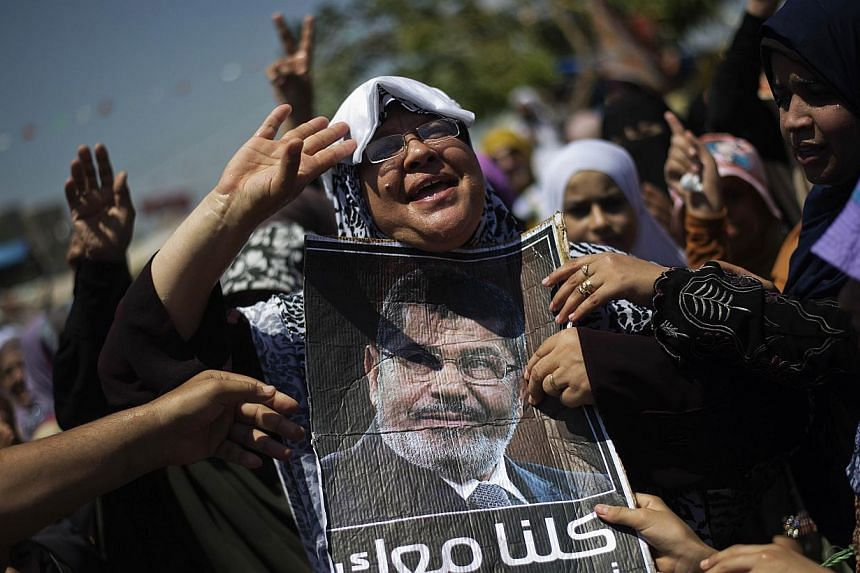 Members of Egypt's Muslim Brotherhood and supporters of ousted president Mohamed Mursi shout political and religious slogans as they take part in a sit-in outside Cairo, Rabaa al-Adawiya mosque on Wednesday, Aug 7, 2013. Egypt's Prime Minister Hazem