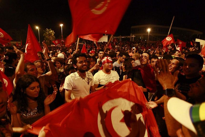 """Anti-government protesters wave national flags during a demonstration in Tunis Aug 6, 2013. Tunisia's political crisis neared its """"moment of truth"""" on Wednesday after tens of thousands of people poured onto the streets of the capital to demand the go"""