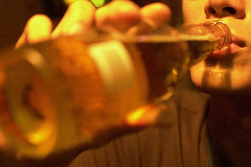 Posed photo of a man drinking alcohol. A doctor allegedly took his two teenage sons to a gun club, smuggled his elder son into a nightclub to drink alcohol and let both play video games until the early hours of the morning. -- ST FILE PHOTO:&nbs