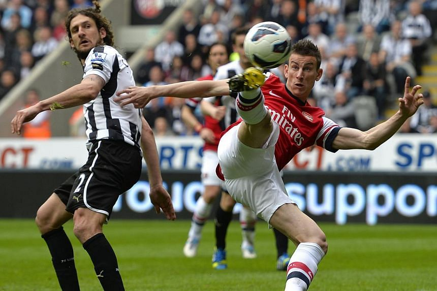 Arsenal's Laurent Koscielny (right) scores against Newcastle United during their English Premier League soccer match at St James' Park in Newcastle, northern England, on May 19, 2013. StarHub has doubled its rebate for subscribers who choose to