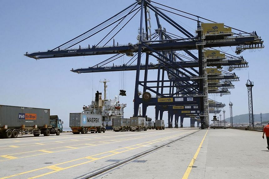 A worker walks past trucks as they line up to load containers onto a ship at a port in Ningbo, Zhejiang province in this July 9, 2013 file photograph.China's monthly trade surplus fell 29.6 per cent in July year-on-year to US$17.8 billion (S$23