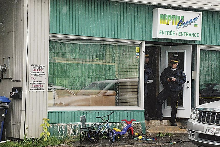 Police stand in front of the Reptile Ocean store in Campbellton, New Brunswick August 5, 2013 after an incident in which an African rock python escaped its enclosure, got into the store's ventilation system and apparently strangled two young boys as