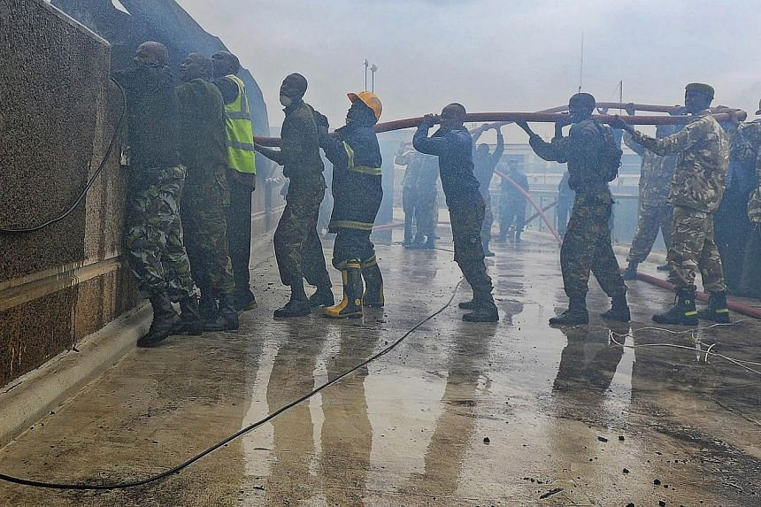 A combined force of fire fighters, military and police spray water canon at the still smouldering terminal at the Jomo Kenyatta International airport in Nairobi on Aug 7, 2013.-- PHOTO: AFP