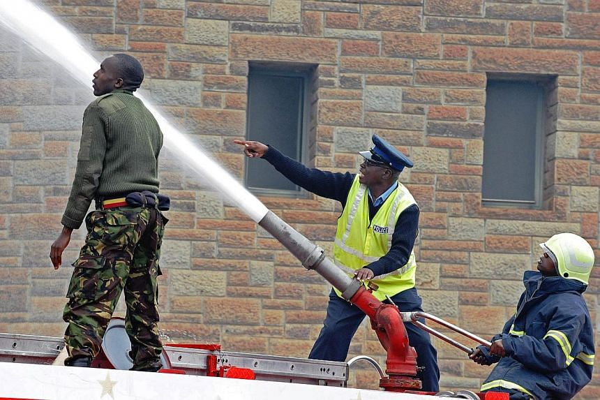 Firefighters shoot a water canon to control a blaze outside the burning Jomo Kenyatta International airport in Nairobi on Aug 7, 2013.-- PHOTO: AFP