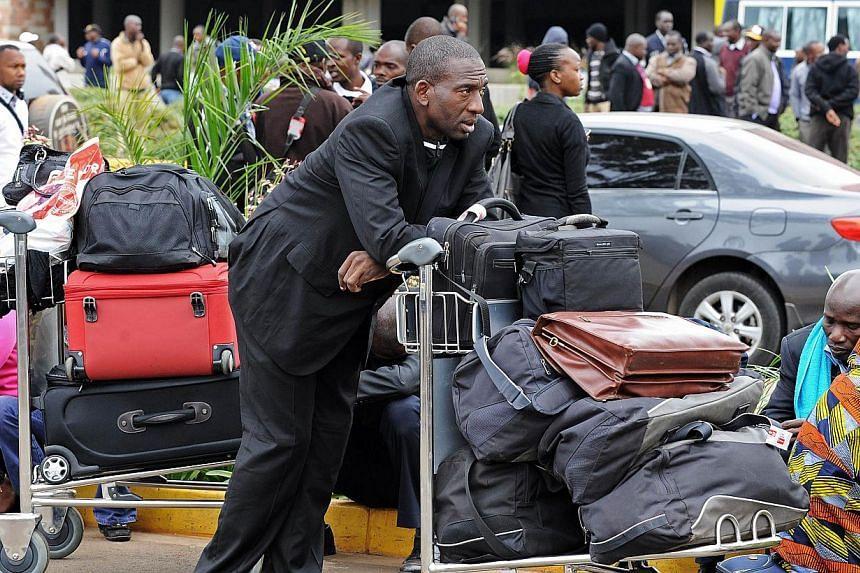 Stranded passengers wait outside the Jomo Kenyatta International Airport in Nairobi on Aug 7, 2013. -- PHOTO: AFP