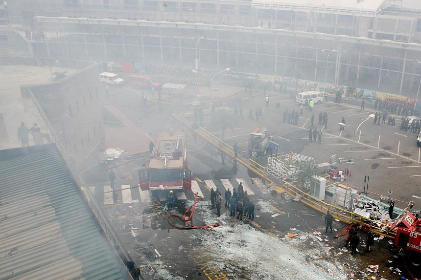 Fire crews and debris are pictured outside Jomo Kenyatta international airport in Nairobi on Aug 7, 2013.-- PHOTO: AFP