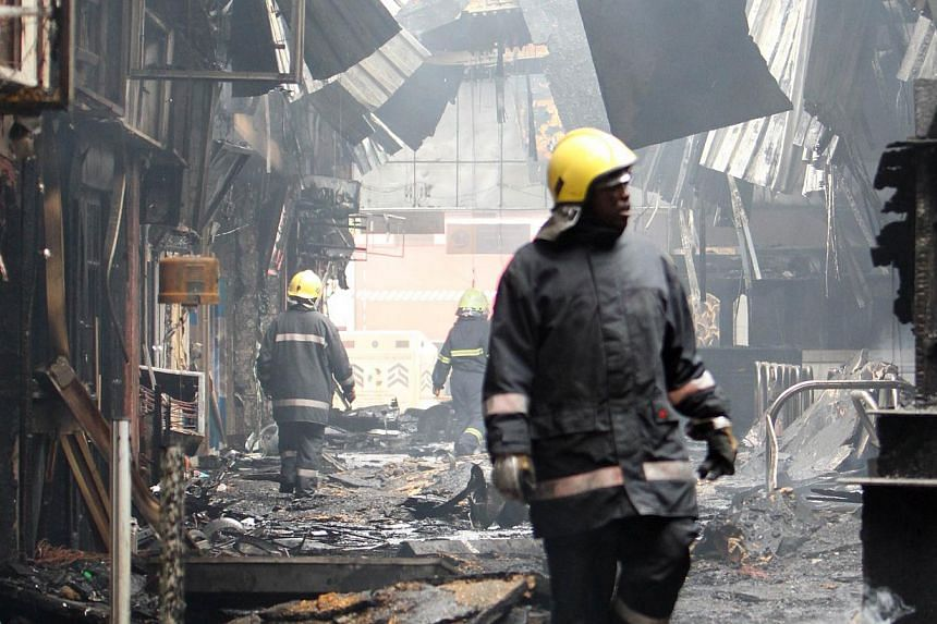 Firefighters walk through the debris after a fire damaged a terminal at the Jomo Kenyatta international airport in Nairobi on Aug 7, 2013.-- PHOTO: AFP