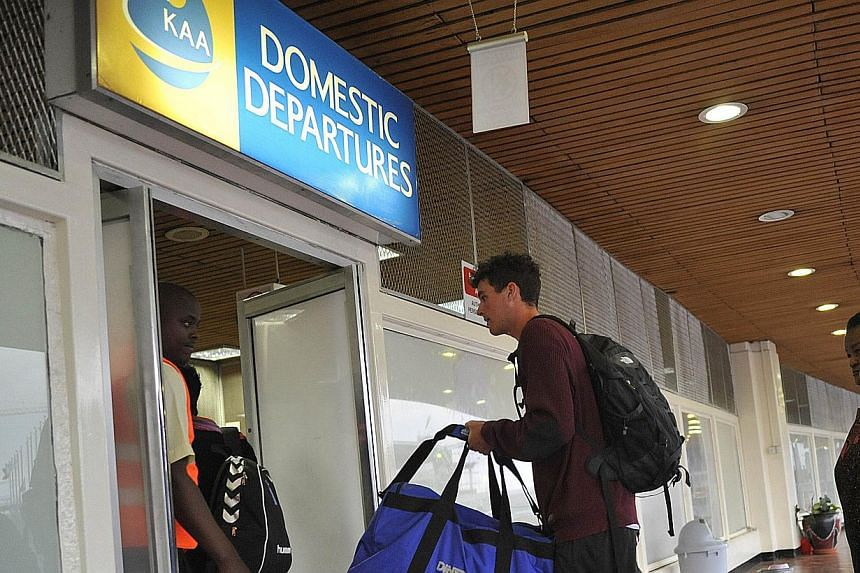 Passengers get through the security check at the Jomo Kenyatta International Airport in Nairobi on Aug 7, 2013, shortly after local flights resumed normal operation following after it was ravaged by fire. -- PHOTO: AFP