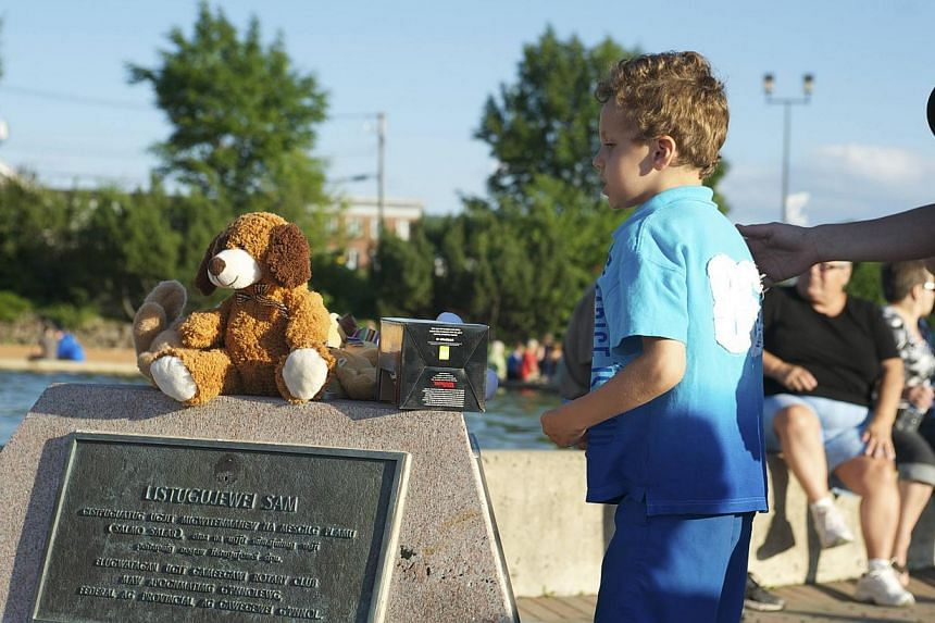 Ethan Levesque-Pelletier looks at some toys left at a makeshift memorial during a vigil for Noah and Connor Barthe in Campbellton, New Brunswick on Aug 7, 2013.-- PHOTO: REUTERS