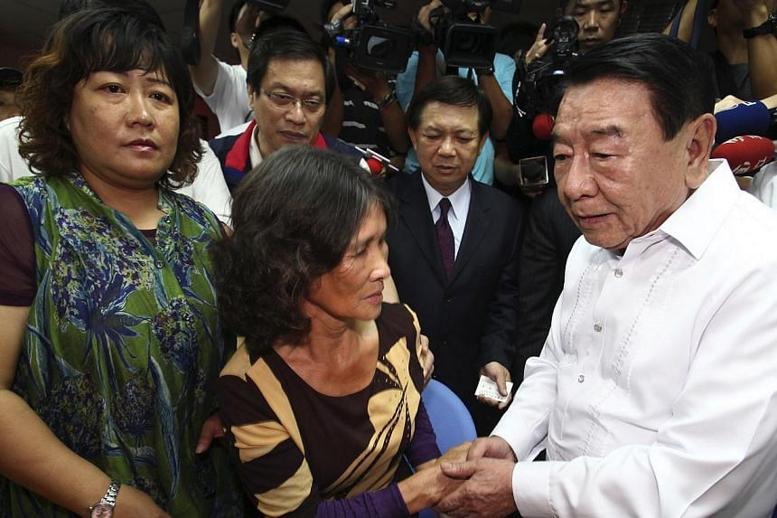 Chairman of the Manila Economic and Cultural Office Amadeo R. Perez (right) shakes hands with Hung Chen A-lun (centre), widow of Taiwanese fisherman Hung Shih-cheng, during a news conference in Liuqiu, in Pingtung County, southern Taiwan on Thursday,