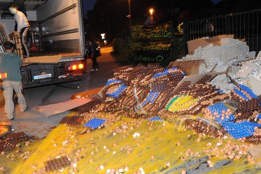 French egg producers throw crates of eggs from the back of a truck onto the sidewalk in front of the taxes and internal revenue service office in Carhaix-Plouguer, Brittany, western France, during a protest action, on Aug 7, 2013. -- PHOTO: AFP