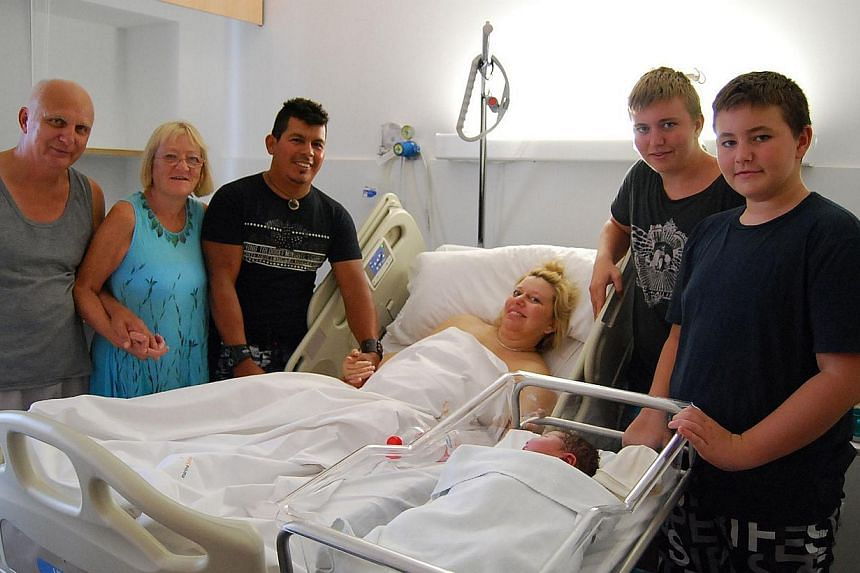 This handout photo obtained from the Hospital Marina Salud in Denia on Aug 7, 3013, shows 40-year-old British woman Maxime Marin (centre) surrounded by family members after giving birth today to the biggest baby ever born naturally in Spain -- a girl
