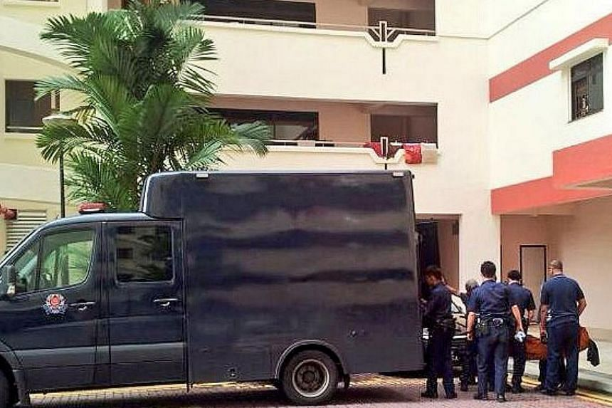 Police take away the dead body of a 41-year-old woman who was found dead in a flat at Choa Chu Kang Avenue 2. -- PHOTO: RACHEL AUYONG