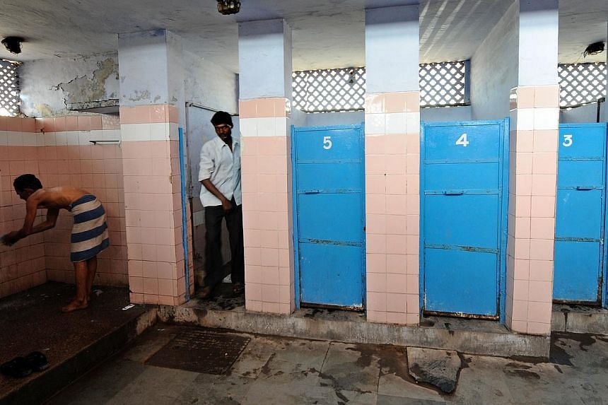 A Indian man (L) washes as another comes out of a toilet in a toilet complex run by an NGO Sulabh International at railway station in New Delhi on April 23, 2011. Fast-growing Asian economies may be flush with money but filthy toilets remain a blight