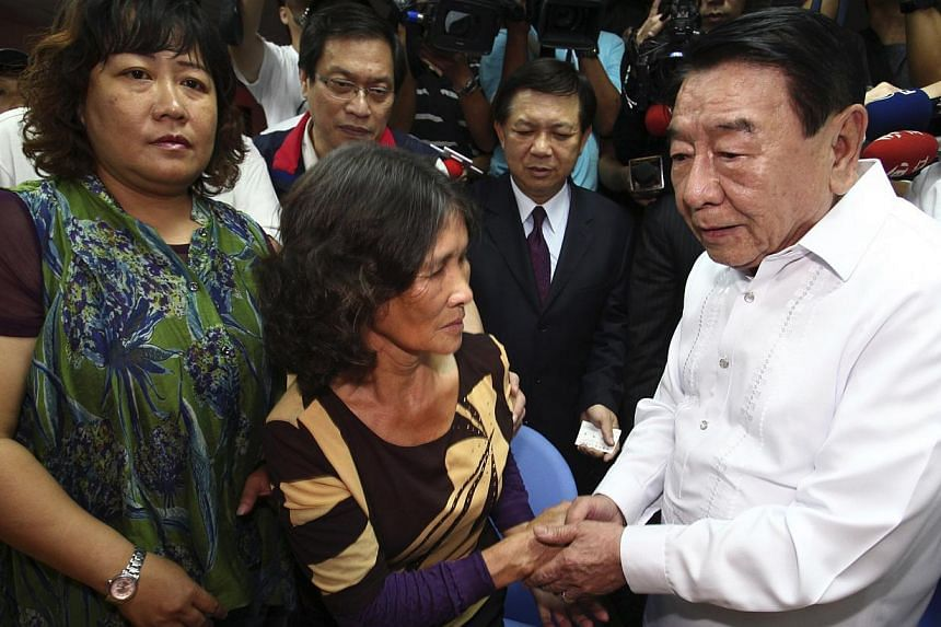 Chairman of the Manila Economic and Cultural Office Amadeo R. Perez (right) shakes hands with Mrs Hung Chen A-lun (centre), widow of Taiwanese fisherman Hung Shih-cheng, during a news conference in Liuqiu, Pingtung County, southern Taiwan, on August