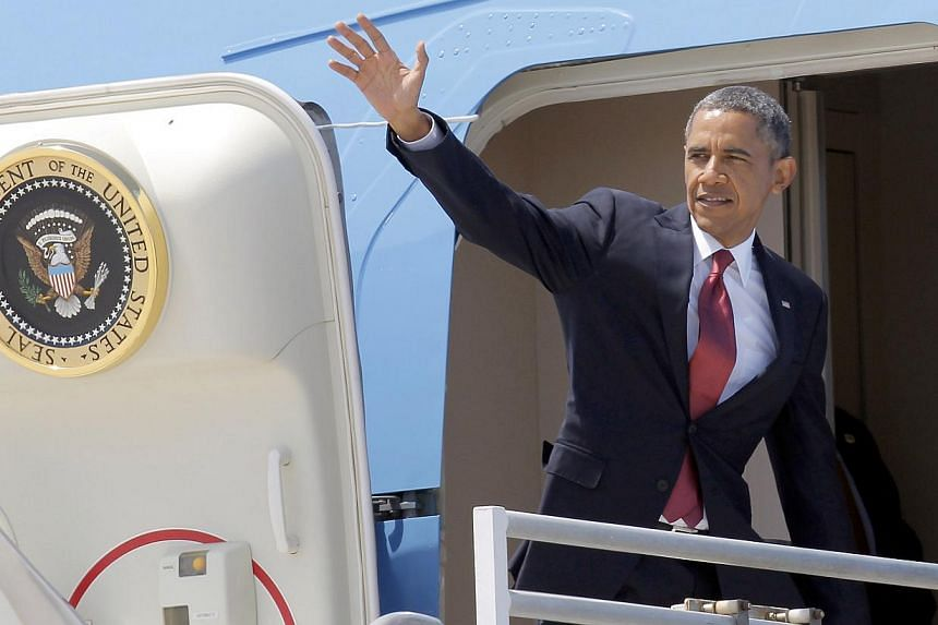 President Barack Obama waves from the door of Air Force One for his return to Washington, after a two-day swing through Southern California, at Los Angeles International Airport on Aug 7, 2013. Mr Obama is headed to swanky Martha's Vineyard on Saturd