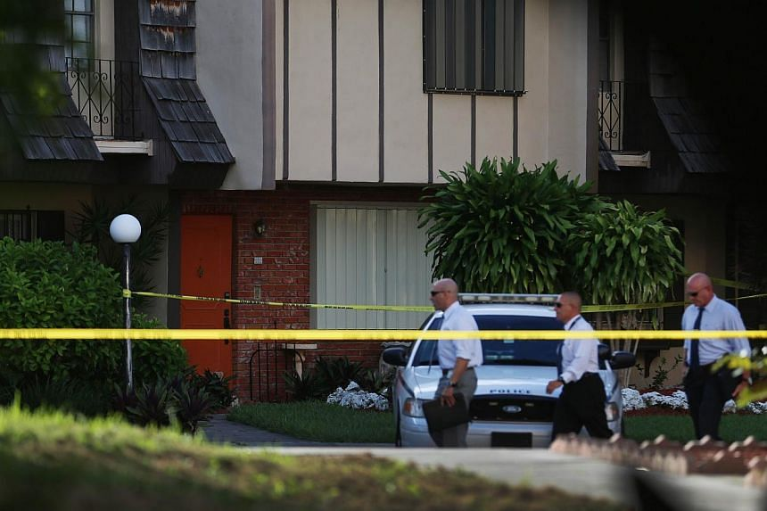 Police detectives walk past the orange door which is the front door to a townhouse where seemingly a husband reportedly confessed on Facebook to murdering his wife on Aug 8, 2013, in Miami, Florida. A man is being held in the United States after appa