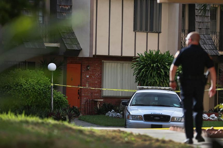 A police car is parked in front of a townhouse where seemingly a husband reportedly confessed on Facebook to murdering his wife on Aug 8, 2013, in Miami, Florida. A man is being held in the United States after apparently gunning down his wife and pos