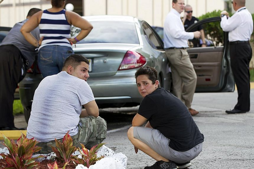 Two people sit behind a police car as Miami police officers investigate a murder in Miami on Aug 8, 2013. A man is being held in the United States after apparently gunning down his wife and posting a gruesome picture of her dead body on Facebook, aut